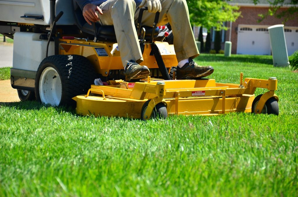 yellow riding lawn mower - grass clippings
